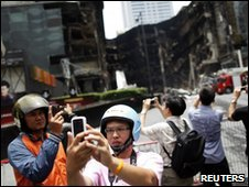 Passers-by take pictures of burned-out buildings in Bangkok on 24 May 2010