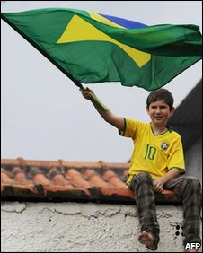 A boy waves a Brazilian flag as he sits on a roof to watch Brazil's national football team train on 23 May