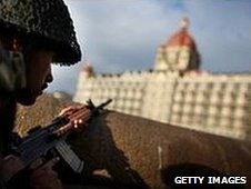 An Indian soldier surveys the Taj Mahal Palace Tower Hotel in Mumbai, during the attack in November
