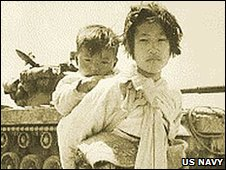 A Korean girl with her brother on her back in front of an M-26 tank in Haengju