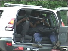 Jamaican police officers point their guns from inside a police vehicle in Kingston, Jamaica, 25 May 2010