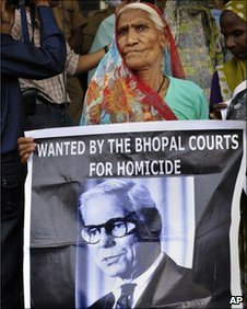 An elderly survivor holds a poster of Warren Anderson as she waits for a verdict in Bhopal, India, Monday, June 7, 2010
