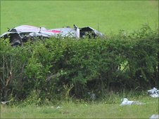 The remains of the crashed Subaru car can be seen behind a hedge