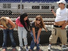 Residents expose their buttocks to a passing Amtrak train