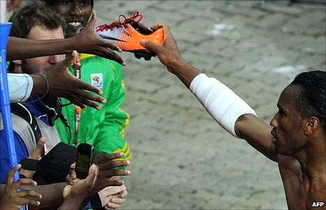 Ivory Coast's striker Didier Drogba (right) gives his shoe to a supporter after the Group G first round 2010 World Cup football match Ivory Coast versus North Korea