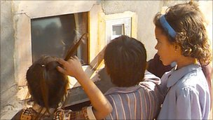 Children using computer via a hole in a wall