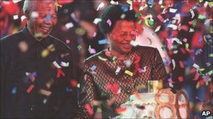 Nelson Mandela with his new wife, Graca Machel, next to his birthday cake, at a reception held at Gallagher Estate outside Johannesburg Sunday, 19 July 1998
