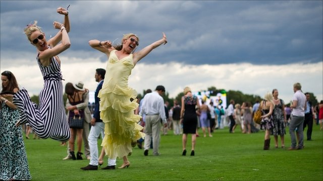 Two guests jump into the air for their friend's photograph during half-time at the Cartier International Polo day