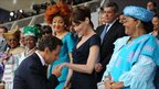 French President Nicolas Sarkozy (centre) kisses the hand of his wife, France's first lady Carla Bruni-Sarkozy surrounded by the first ladies of some African countries during the annual Bastille Day military parade in Paris 14 July 2010
