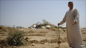 A Bedouin man holds an olive tree root near a destroyed building in al-Arakib