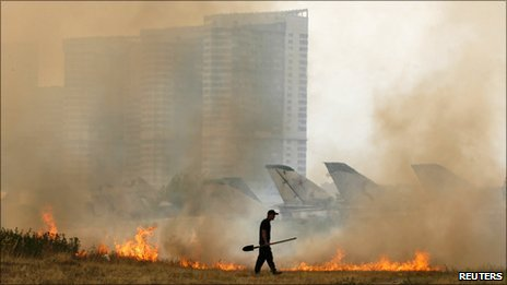 A security guard walks near a fire caused by the heatwave at an aviation museum in Moscow, 29 July 2010