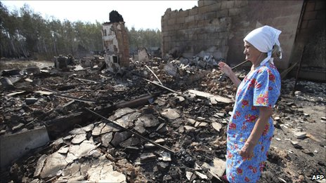 An old woman surveys her fire-ravaged home in Voronezh, central Russia, 1 August