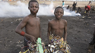 Greenpeace photo of boys with a bundle of electrical cables and other electronic components in Accra, Ghana, 2008. The cables are burned to extract the copper, a process that releases toxic chemicals into the environment.