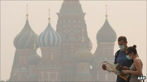 People wear face masks to protect themselves from the forest fire smog in Moscow on August 4, 2010