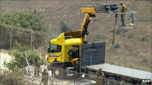Israeli soldiers use a crane as they appear to cut down a tree on the Lebanese side of the fenced border, near the village of Adaysseh on 3 August.