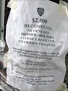 A sign offers a reward for help solving a violent crime