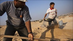 Saleh al-Dama, 38, and son Ali, 11, dig for gravel in Beit Lahiya, Gaza Strip, July 2010