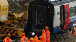 Workers surround the derailed train