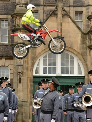 Lee Lucas, 16, of the IMPS motorcycle display team, jumps over Second Lieutenant Miles Evans, 21, and other members of the Citadel Military College of South Carolina Band and Pipes at the Redford Barracks in Edinburgh ahead of the Royal Edinburgh Military Tattoo.