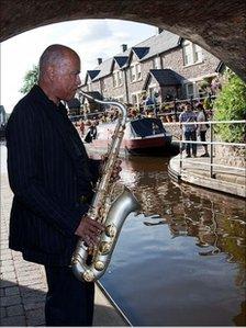A saxophonist under a bridge at Brecon jazz