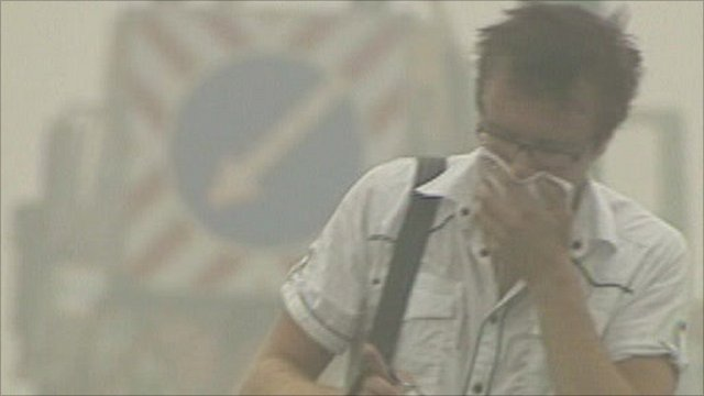 Man covers face while walking through smog in Moscow