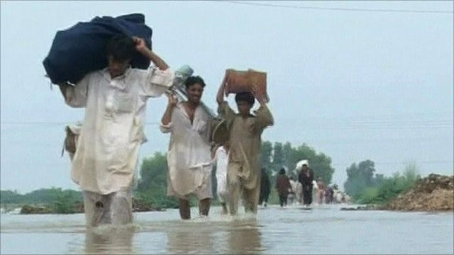 Men carrying belongings on back through floodwater