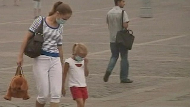 Masked woman and child in Moscow