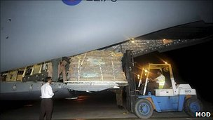 Forklift truck loads tents on to C17 aircraft