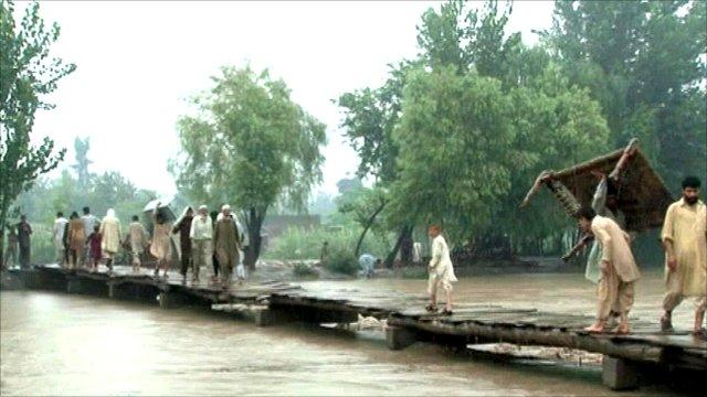 Villagers cross a bridge from Khazana