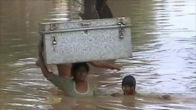 A woman and a child in flood waters