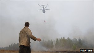 A man watches as a helicopter dumps water on a blaze in Russian's Ryazan region, 9 August