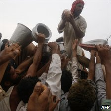 Pakistani flood victims crowd around supplies of food relief