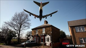 Plane passing over house