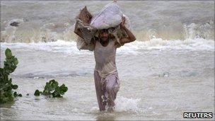 Man in flood waters in the Muzaffargarh district of Punjab province