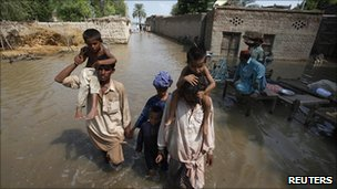 A family wades through waters in the village of Karam Pur near Sukkur in Sindh province