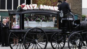 A horse drawn hearse carries the coffin of Suzanne Blamires
