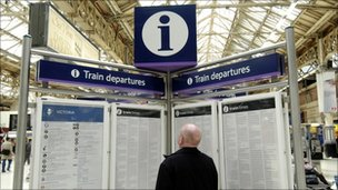 A passenger inspects a train timetable