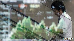A man in Japan while a graph of the Yen against the US dollar is reflected