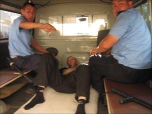 Kazakh police van with injured prisoner - one of 38 inmates who mutilated themselves in July (Image: Vadim Kuramshin)