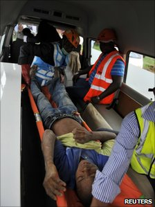 An injured man is taken away in an ambulance after the building collapse in Abuja (12 August 2010)