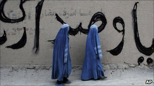 Afghan women pass a parliamentary elections graffiti in Mazar-i-Sharif on 22 July 2010