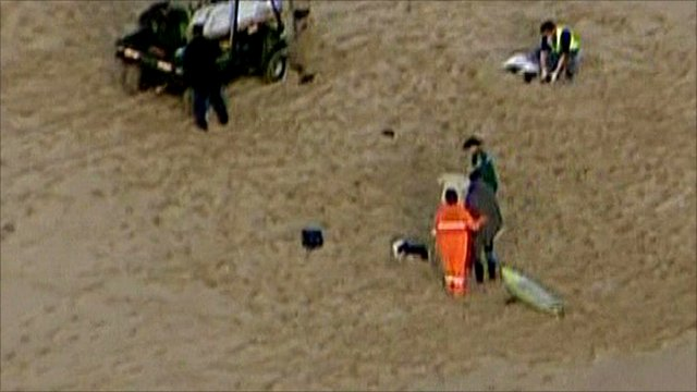 Aerial view of victim in back of vehicle on beach