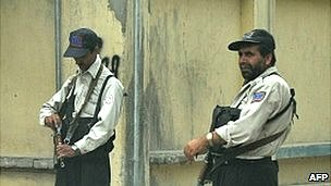 Private security personnel stand guard on a Kabul street (file photo)