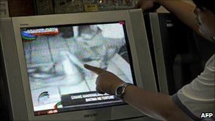 A woman points at the screen as she watches a TV broadcast that includes mobile phone footage of police allegedly torturing a naked man in Manila (18 August 2010)