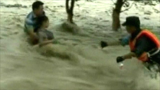 Woman is rescued from torrential water
