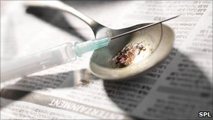 A hypodermic needle and syringe with heroin on a spoon