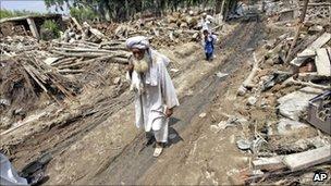 Flood survivors walk amid debris in Nowshera on 17 August 2010