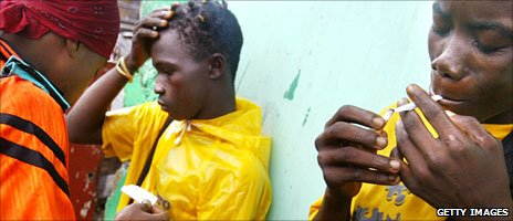 Teenagers loyal to the Liberian army smoke marijuana in Monrovia in July 2003