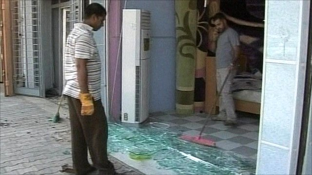 Baghdad shopkeepers cleaning up broken glass after explosion