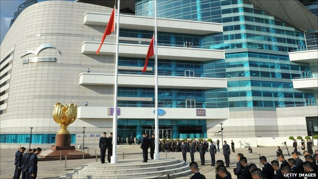 Officials gather with bowed heads around flags at half-mast in Bauhinia Square in Hong Kong